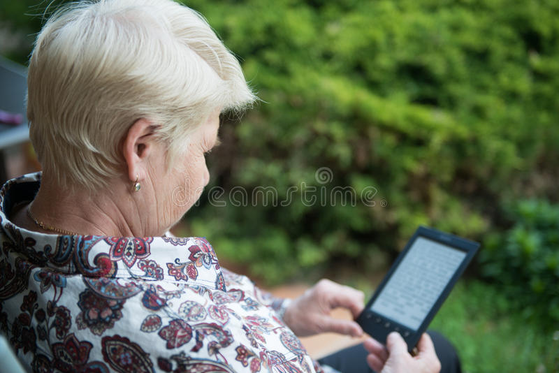 Älteres Frauenlesungs-eBook lizenzfreie stockfotos