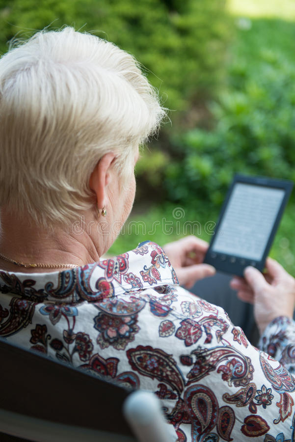 Älteres Frauenlesungs-eBook lizenzfreies stockfoto