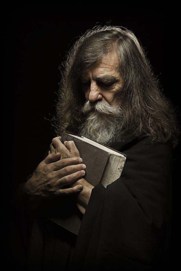 Älteres Gebet, alter Mann, der mit den Händen auf Bibel-Buch, über Querstation betet stockfotos