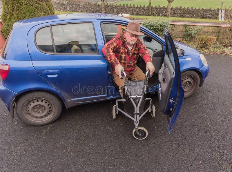 Älteres Gehen des männlichen Mannes des hohen Alters zum Auto mit Unfähigkeit MOBILITÄT LEICHTES ROLLATOR TRI WANDERER-GEHENDEN R lizenzfreies stockfoto