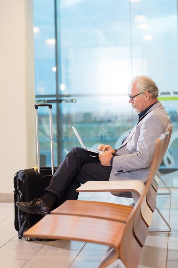 Älteres Geschäftsmann-Using Laptop At-Flughafenabfertigungsgebäude stockfoto
