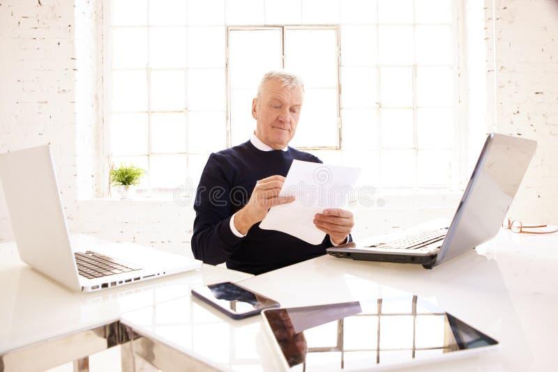 Älteres Geschäftsmannholdingdokument in seiner Hand beim Sitzen am Schreibtisch und am Arbeiten stockfotografie