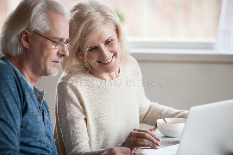 Älteres glückliches Paar, das mit dem Laptop isst Frühstück toget genießt lizenzfreie stockbilder