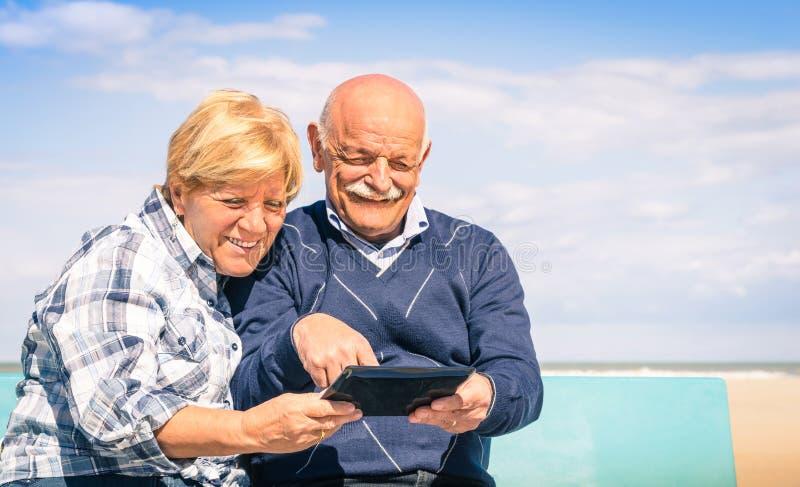 Älteres glückliches Paar, das Spaß mit einer Tablette am Strand hat stockbilder