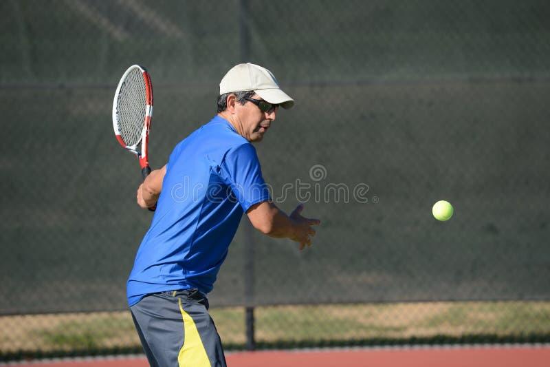 Älteres hispanisches spielendes Tennis stockbild