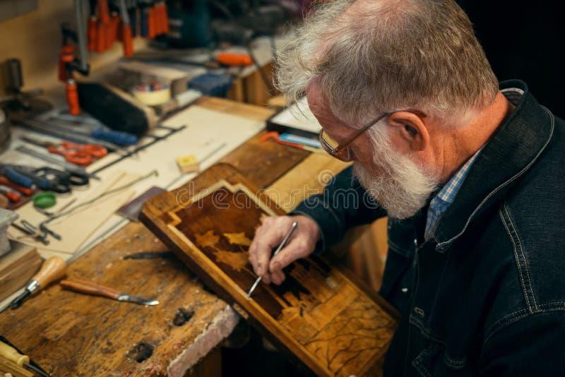 Älteres Holz, das Fachmann während der Arbeit schnitzt stockfoto