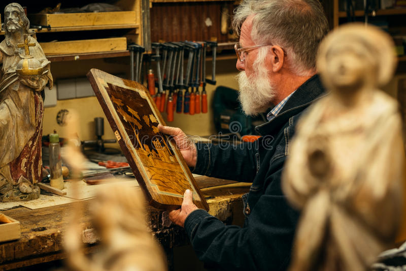 Älteres Holz, das Fachmann während der Arbeit schnitzt lizenzfreie stockfotografie
