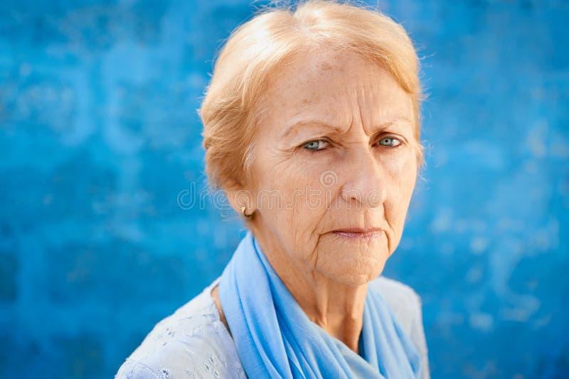 Traurige alte blonde Frau, die Kamera betrachtet lizenzfreie stockbilder