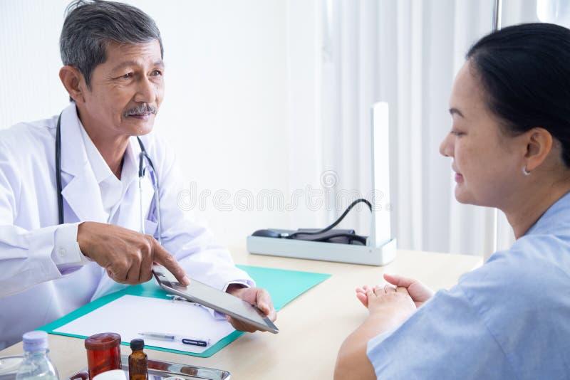 Älteres männliches Doktorlächeln, das mit dem Sprechen mit seinem älteren Patienten sich bespricht stockbilder