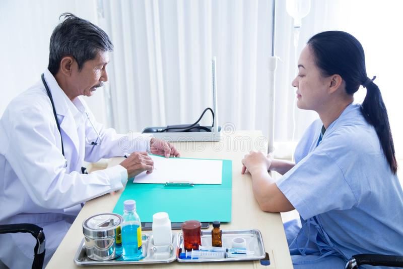 Älteres männliches Doktorlächeln, das mit dem Sprechen mit seinem älteren Patienten sich bespricht lizenzfreie stockfotografie