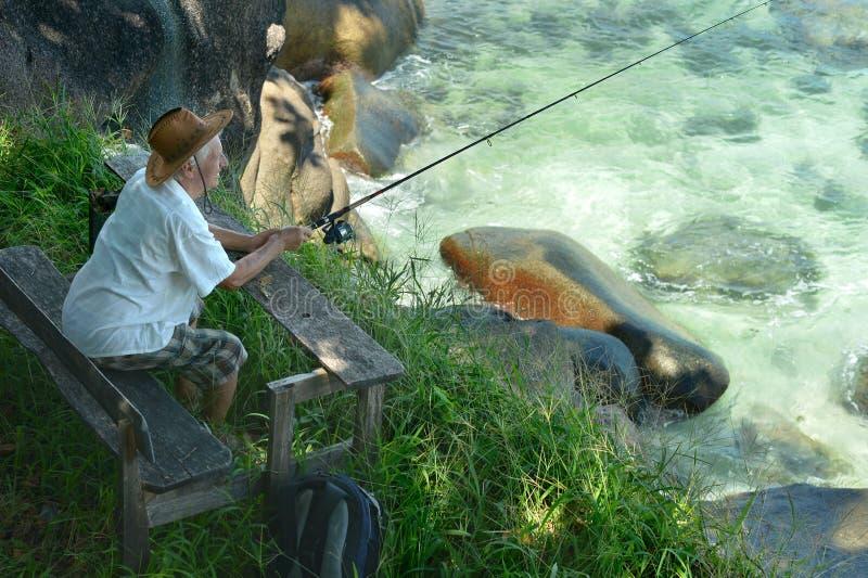 Älteres Mannfischen im Meer mit lizenzfreie stockfotos