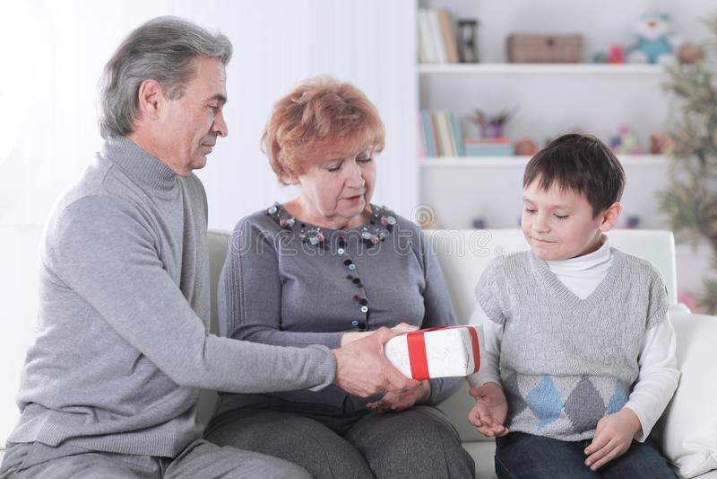 Älteres Paar gibt ihrem Enkel auf seinem Geburtstag ein Geschenk lizenzfreies stockfoto