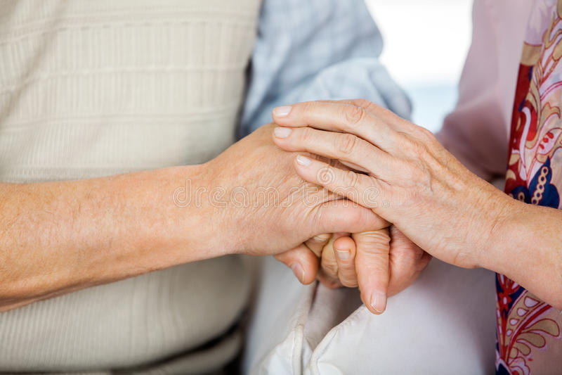 Älteres Paar-Händchenhalten beim an sitzen lizenzfreies stockfoto
