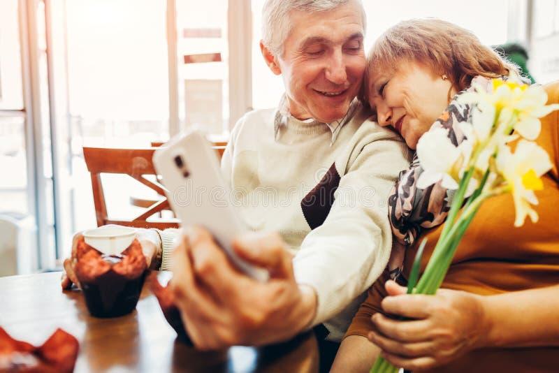 Älteres Paar macht ein selfie unter Verwendung eines Telefons im Café Feiern des Jahrestages stockbild
