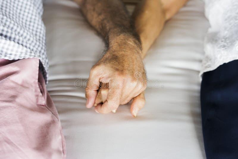 Älteres Paarhändchenhalten an einem Erholungsort stockbild