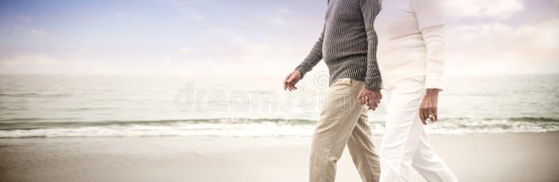 Älteres Paarhändchenhalten und Gehen auf den Strand stockbild