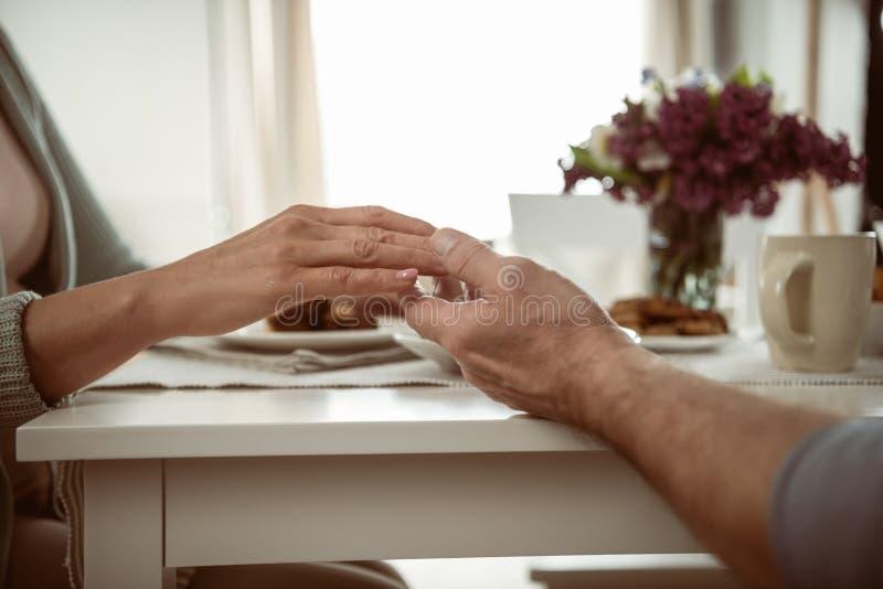 Älteres Paarhändchenhalten während des Frühstücks lizenzfreies stockfoto