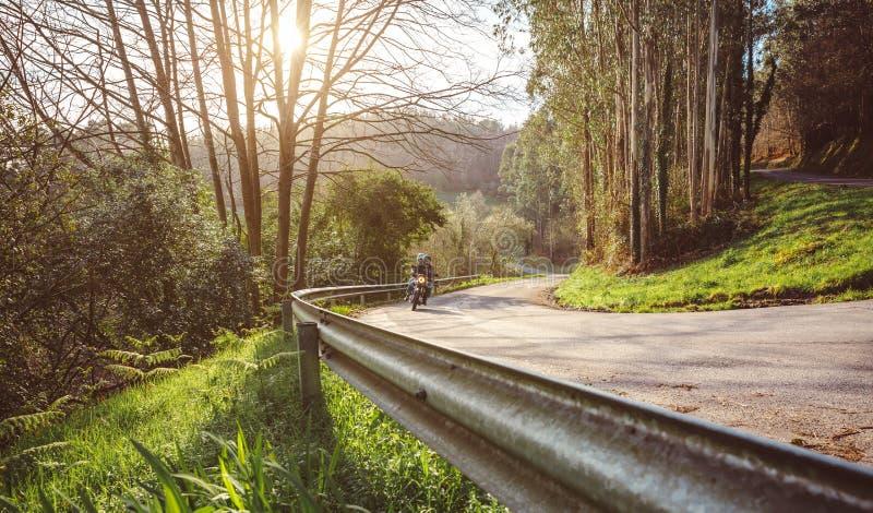 Älteres Paarreitmotorrad entlang Waldweg lizenzfreie stockfotografie