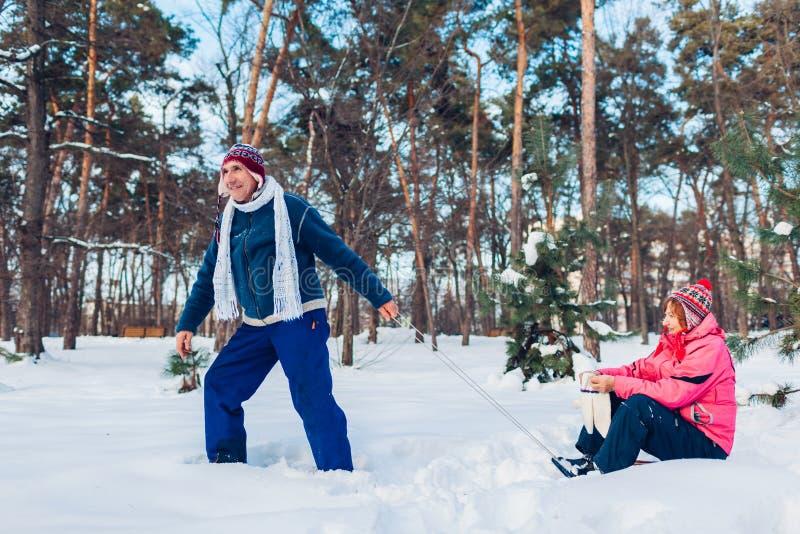Älteres Paarrodeln Mann, der seine Frau auf Pferdeschlitten trägt Familie, die Spaß in Winter Park hat Valentinsgruß `s Tag stockfotos