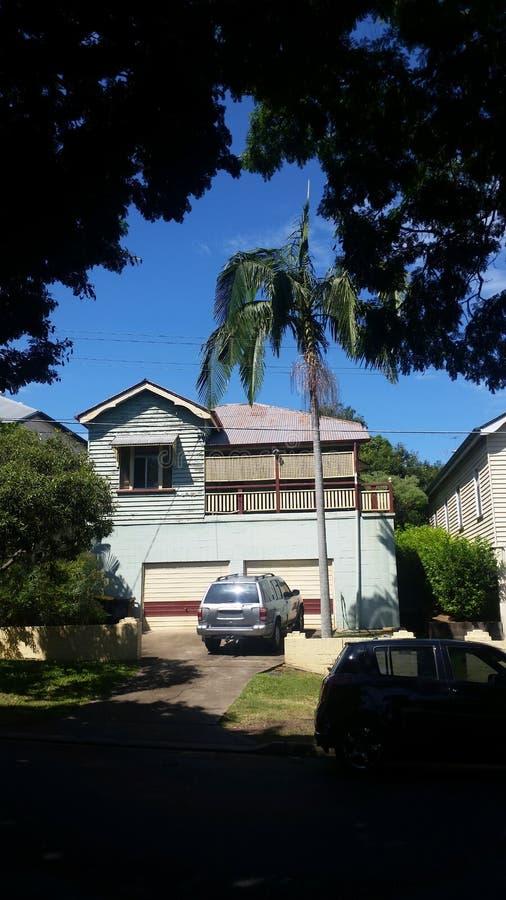 Älteres Queenslander-Haus mit Betonblockgarage darunterliegend und Auto parkte in der Fahrstraße, die durch Schatten und Grün mit stockfotografie