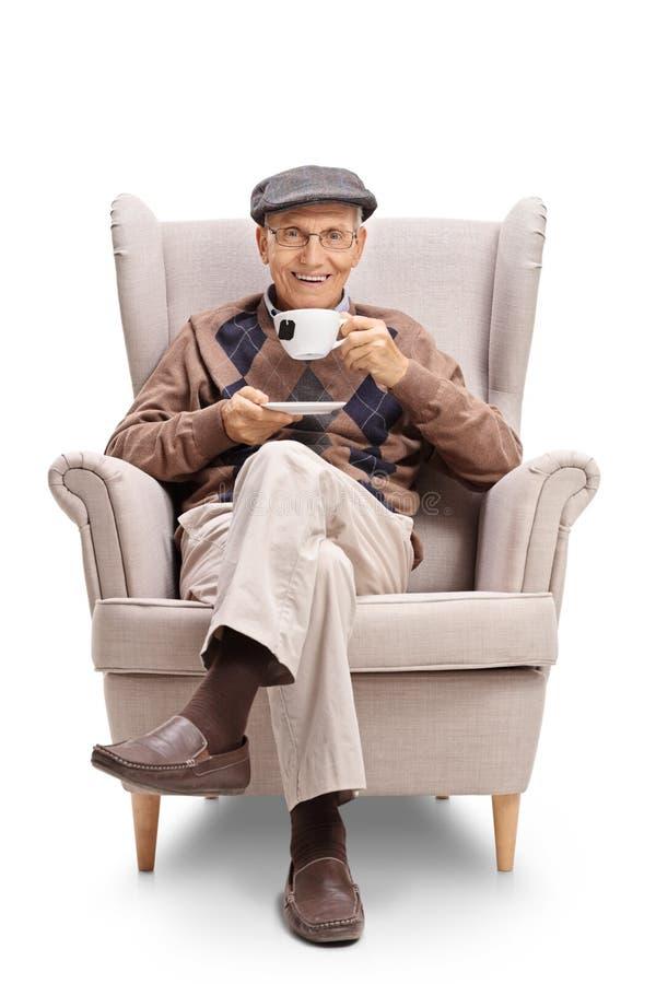 Älteres Sitzen in einem Lehnsessel und Essen einer Tasse Tee stockfotos