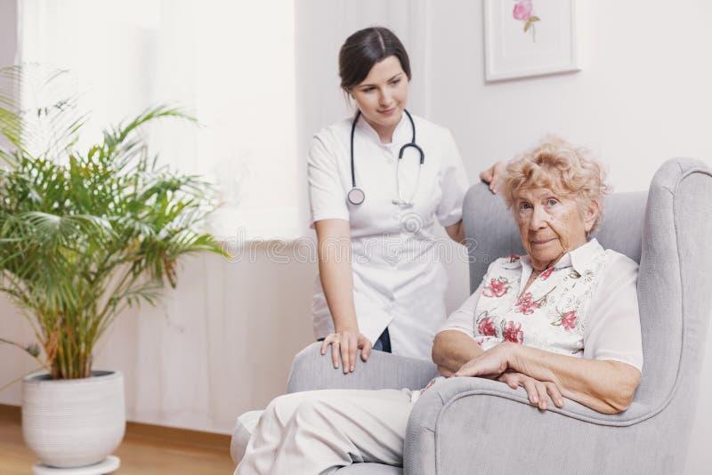 Älteres Sitzen im Lehnsessel am Pflegeheim, Unterstützungskrankenschwester hinter ihr lizenzfreie stockfotos