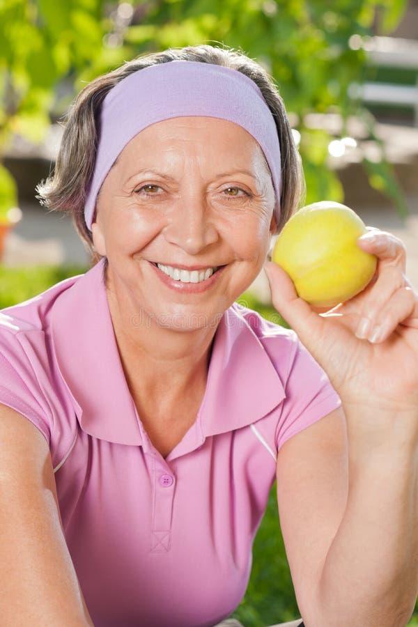Älteres sportives Frauenlächeln isst den im Freienapfel lizenzfreie stockfotografie