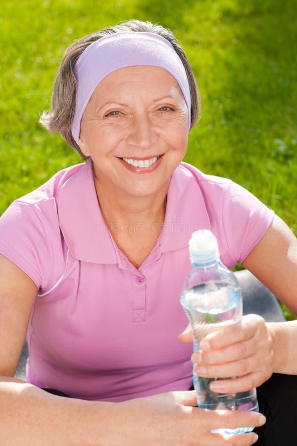 Älteres sportives Frauenlächelneinfluß-Flaschenwasser stockbild