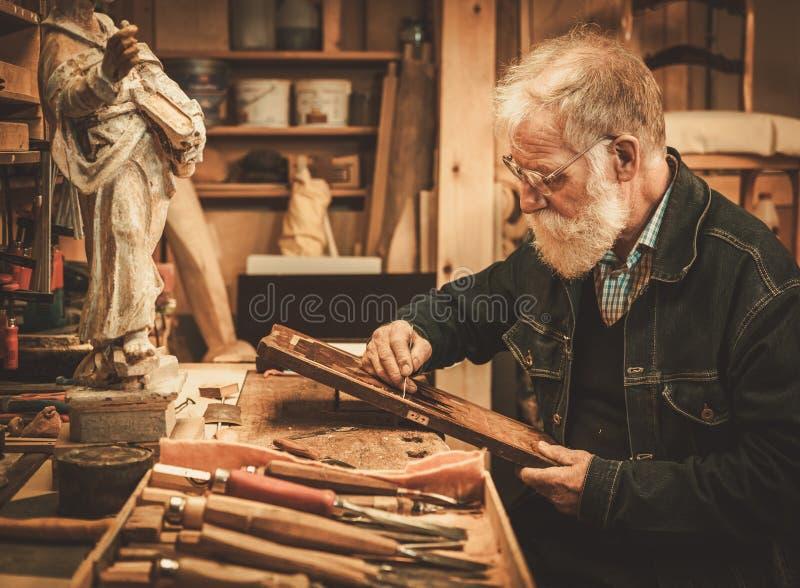 Älteres Stärkungsmittel, das mit antikem Dekorelement in seiner Werkstatt arbeitet lizenzfreies stockfoto