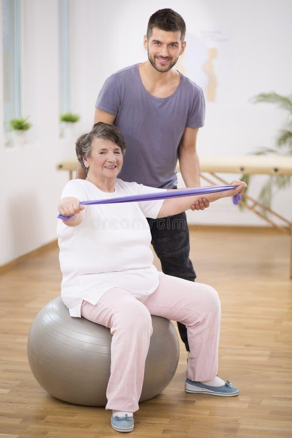 ?lteres Stationieren auf dem ?bungsball w?hrend der Physiotherapie mit ihrem jungen Lehrer stockfoto