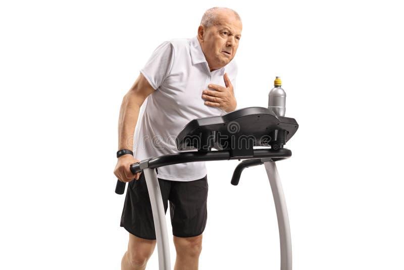 Älteres Trainieren auf einer Tretmühle und Haben eines Herzinfarkts stockbilder