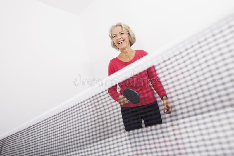 Älteres weibliches Tischtennis-Spielerlachen lizenzfreie stockfotos