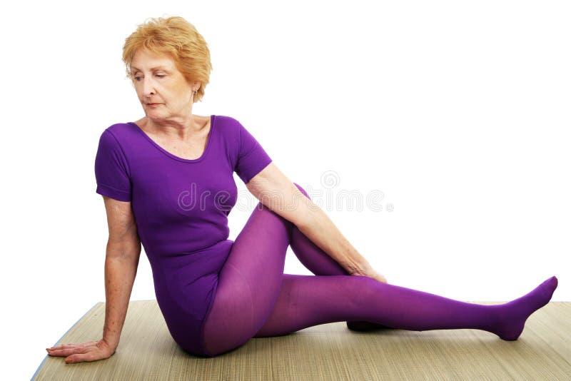 Älteres Yoga - spinale Torsion stockfotos