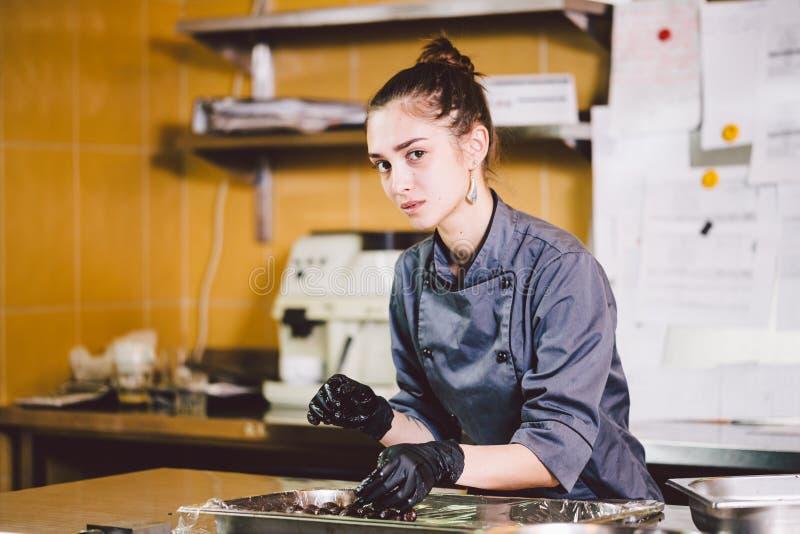 Ämnesyrke och laga matbakelse ung Caucasian kvinna med tatueringen av konditor i kök av restaurangen som förbereder rundan arkivbild