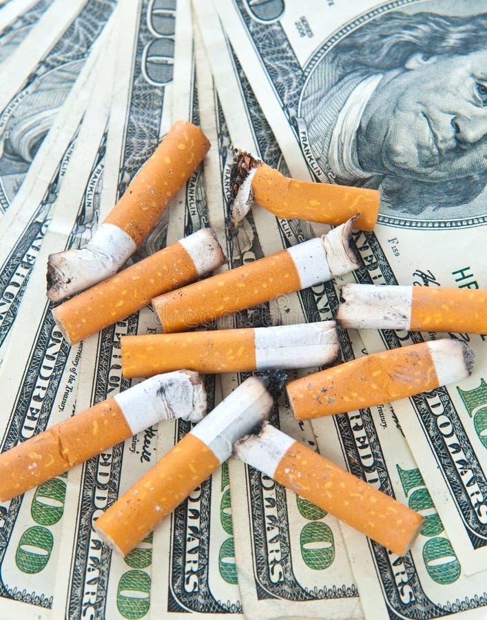 änd cigaretten som lägger pengar royaltyfria foton