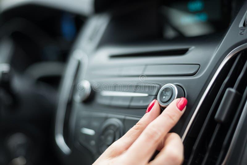 Ändernde Frequenz der Frau auf Autoradio lizenzfreies stockbild