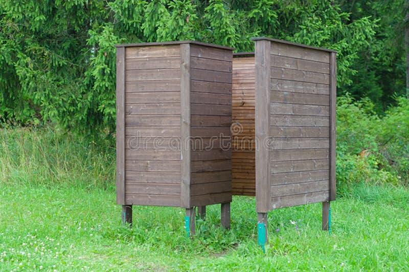 Ändernde Kabine der hölzernen Abnutzung nahe Koniferenwald stockfotos