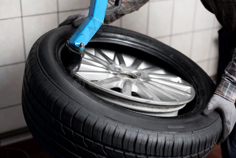 Ändernder Reifen des Mechanikers lizenzfreie stockfotografie