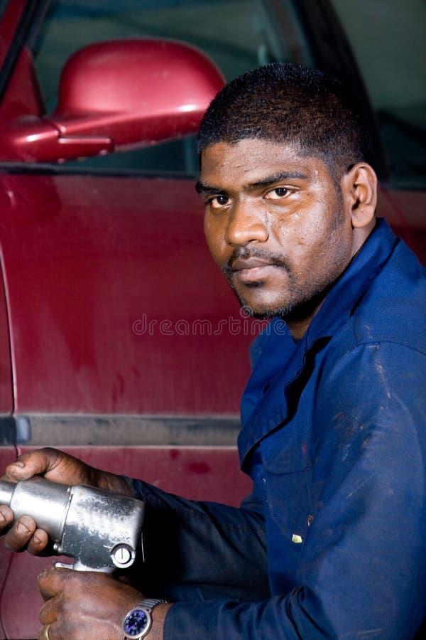 Ändernder Reifen des Mechanikers stockfotografie