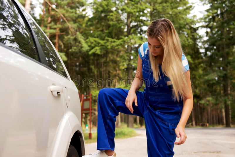 Ändernder Reifen des weiblichen Mechanikers mit Radschlüssel stockfotografie