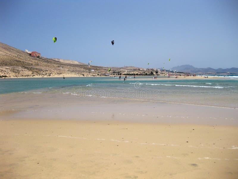 Ändlös bred tideland i lagun med drakesurfare av Gorriones, Playa de Sotavento, Costa calma, Fuerteventura, Spanien royaltyfri foto