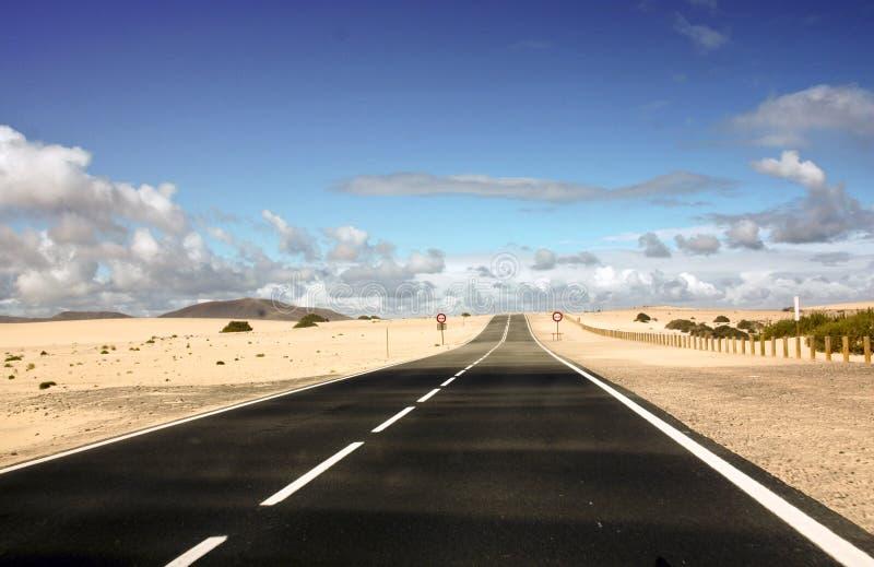 Ändlös kust- väg och sand arkivbild