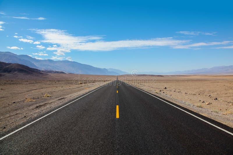 Ändlös och ensam blacktopväg som går in i bergskedjan som skriver in den Death Valley nationalparken royaltyfri fotografi