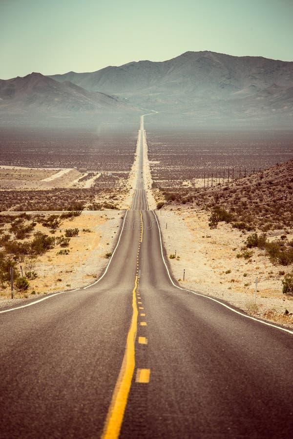 Ändlös rak väg i de amerikanska sydvästerna, USA royaltyfri foto