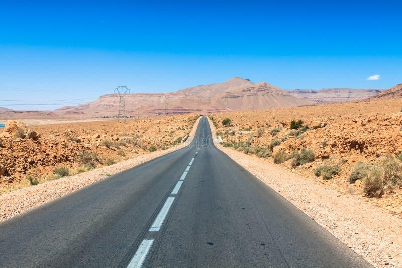 Ändlös väg i Sahara Desert med blå himmel, Marocko Afrika royaltyfria foton