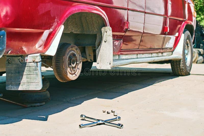 Ändra ett hjul eller ett gummihjul på en röd skåpbil för gammal tappning på utomhus- bilservice royaltyfri bild