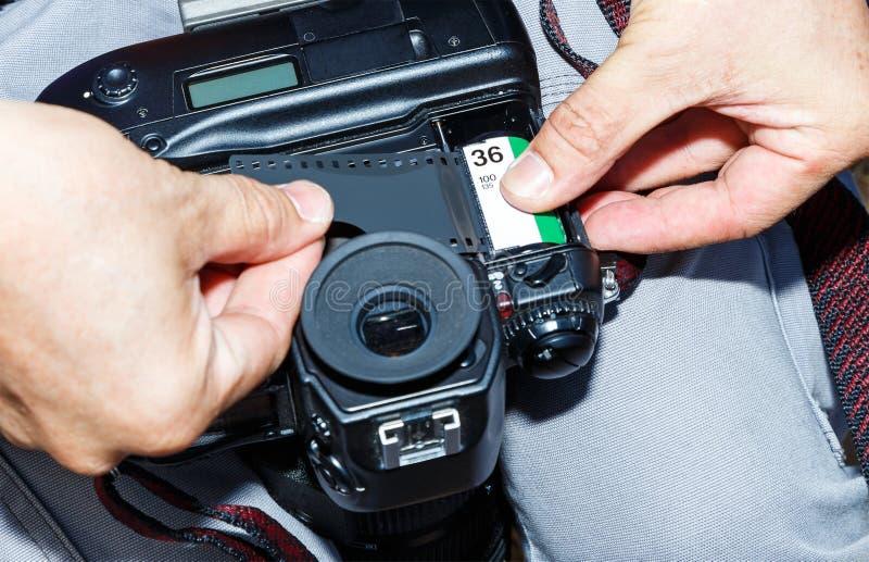 Ändra som är nytt av den negativa rullfilmen in i SLR handbokkamera arkivfoton