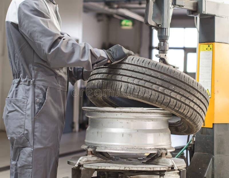Ändrande bilgummihjul för mekaniker. arkivfoto