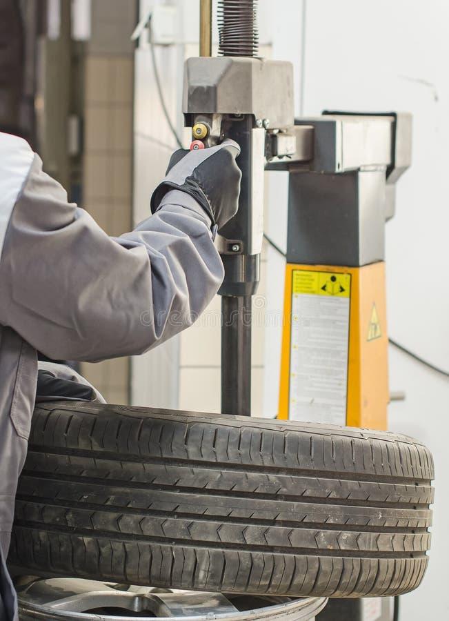 Ändrande bilgummihjul för mekaniker. fotografering för bildbyråer