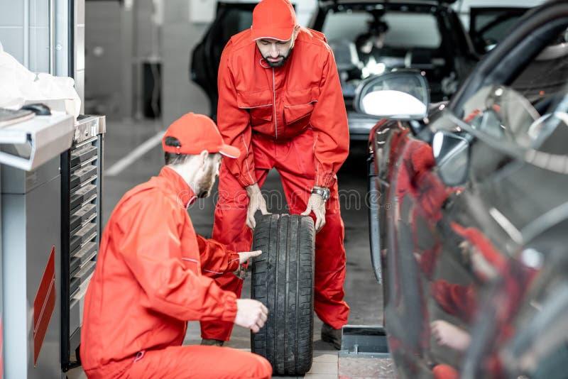 Ändrande hjul för arbetare på bilservicen royaltyfria foton